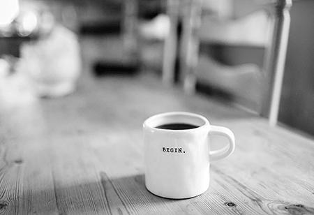 kaffekop på skrivebord med ordet begin
